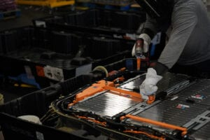 Technician disassembles an electric vehicle battery with an insulated drill and gloves